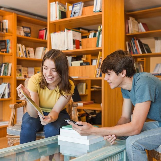 Nette jugendliche, die tablette in der bibliothek betrachten Kostenlose Fotos