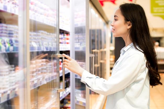 Nette junge asiatin, die milchprodukte am supermarkt wählt Premium Fotos