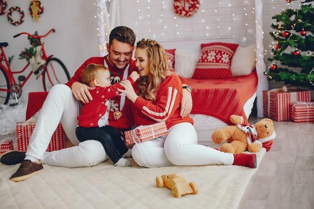 Nette junge familie, die zu hause auf einem bett sitzt Kostenlose Fotos