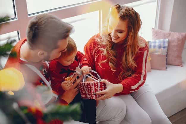 Nette junge familie, die zu hause sitzt Kostenlose Fotos