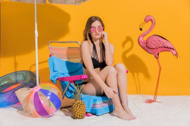 Nette junge frau im badeanzug, der auf wagenaufenthaltsraum im studio stillsteht Kostenlose Fotos