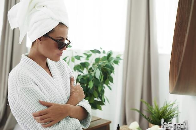 Nette junge frau im bademantel, mit einem weißen handtuch auf dem kopf und einer schwarzen sonnenbrille, die vor dem badezimmerspiegel herumalbert. Premium Fotos