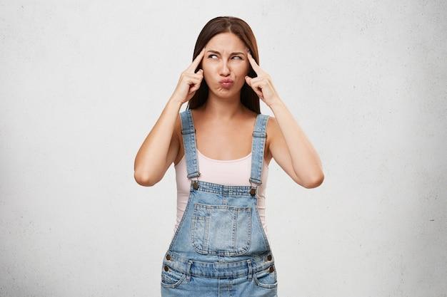Nette junge frau im jeansoverall, die finger an ihren schläfen hält und mit konzentriertem ernstem ausdruck seitwärts schaut, während sie nach lösung für persönliche probleme oder probleme bei der arbeit sucht Kostenlose Fotos