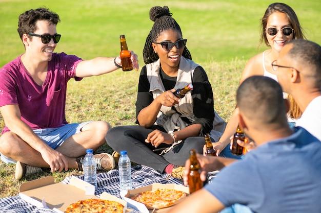 Nette junge leute, die mit bierflaschen im park zujubeln. glückliche freunde, die auf wiese sitzen und bier trinken. freizeit-konzept Kostenlose Fotos