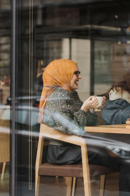 Nette junge moslemische mädchen, die einen kaffee trinken Kostenlose Fotos
