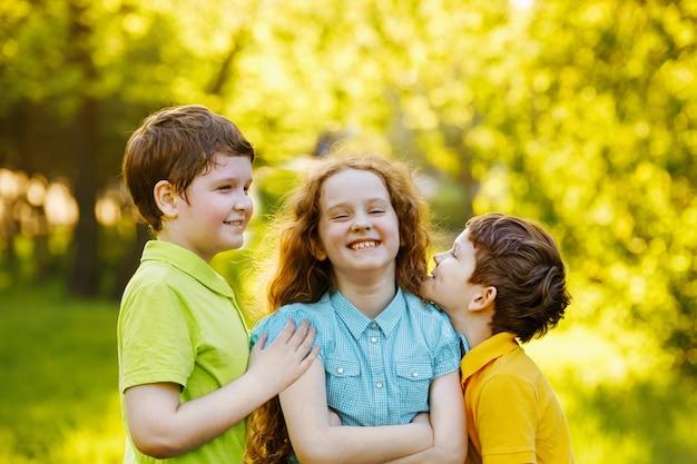 Nette kinder, die im sommerpark stillstehen. familie, glückliche kindheit konzept. Premium Fotos