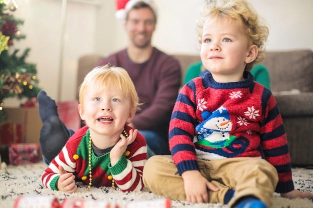Nette kinder, die mit ihren eltern, tragende weihnachtskleidung fernsehen Premium Fotos