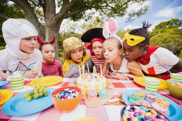 Nette kinder, die zusammen auf der kerze während einer geburtstagsfeier durchbrennen Premium Fotos