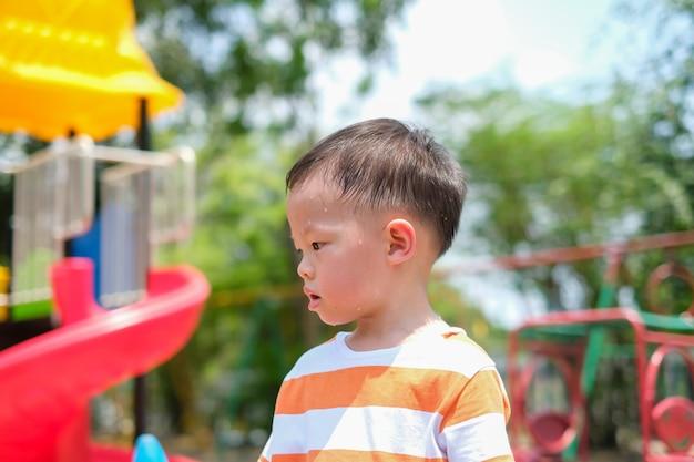 Nette kleine asiatische 2 - 3 jahre alte kleinkindjungenkind, die während des spielens des spaßes, trainieren im freien am spielplatz, hitzschlagkonzept schwitzen Premium Fotos