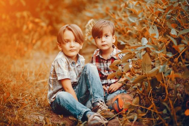 Nette kleine jungen, die in einem park spielen Kostenlose Fotos