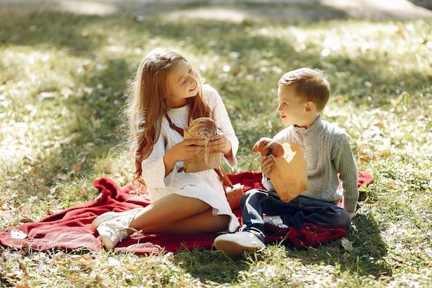 Nette kleine kinder, die in einem park mit brot sitzen Kostenlose Fotos
