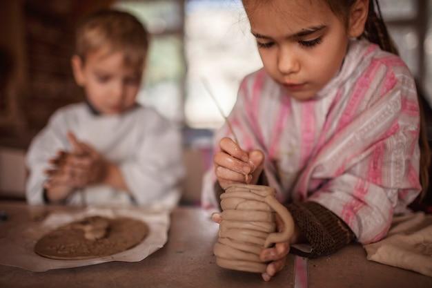 Nette kleine kinder, die zusammen mit modelliermasse in der töpferwerkstatt, im handwerk und in der tonkunst spielen Premium Fotos