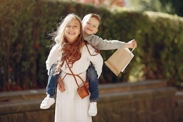 Nette kleine kinder mit einkaufstasche in einer stadt Kostenlose Fotos