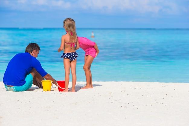 Nette kleine mädchen, die spaß mit vati auf weißem strand haben Premium Fotos