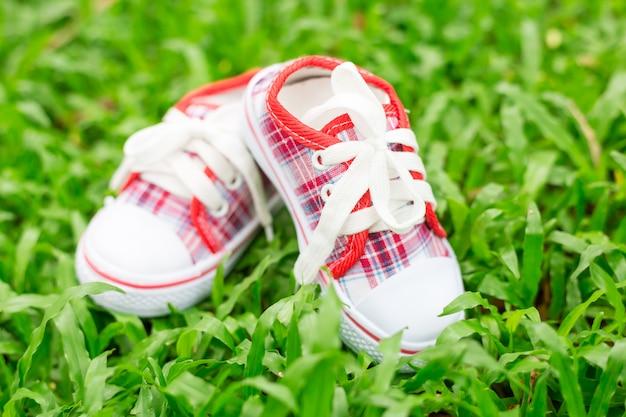 Nette kleine rote und weiße babyschuhe auf grünem gras Premium Fotos