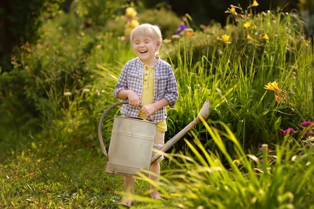 Nette kleinkindjungenbewässerungsanlagen im garten am sonnigen tag des sommers. Premium Fotos