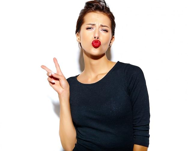 Nette lächelnde modefrau, die in der zufälligen schwarzen kleidung mit den roten lippen auf der weißen wand macht ein entengesicht und zeigt friedenszeichen verrückt geht Kostenlose Fotos
