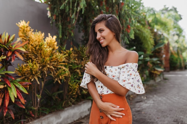 Nette langhaarige frau im hellen rock und in der hellen bluse, die im tropischen garten aufwirft Kostenlose Fotos