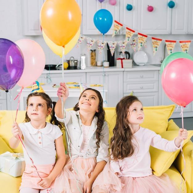 Nette mädchen, die auf dem sofa hält bunte ballone sitzen Kostenlose Fotos