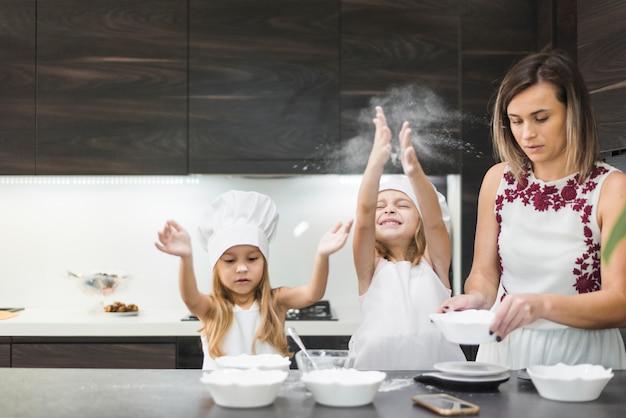 Nette mädchen, die in der küche genießen, während mutter lebensmittel zubereitet Kostenlose Fotos
