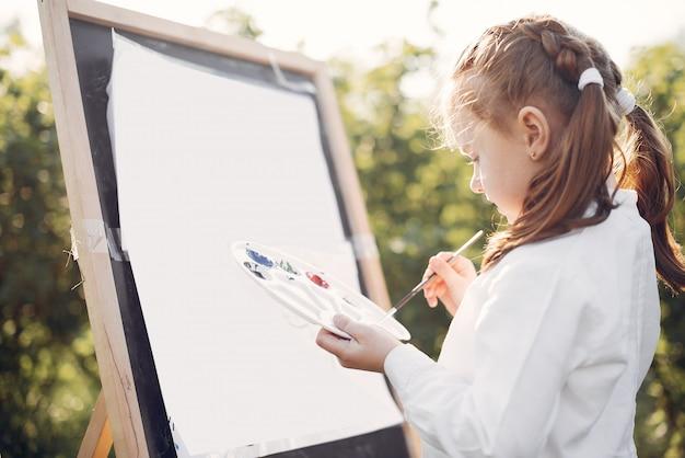 Nette malerei des kleinen mädchens in einem park Kostenlose Fotos
