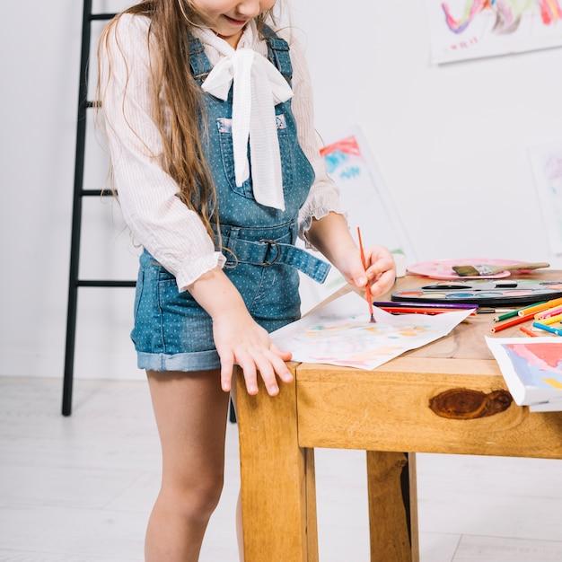 Nette malerei des kleinen mädchens mit aquarell auf papierblatt bei tisch Kostenlose Fotos