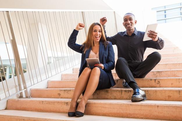 Nette mitarbeiter, die tabletten halten und auf treppe sitzen Kostenlose Fotos