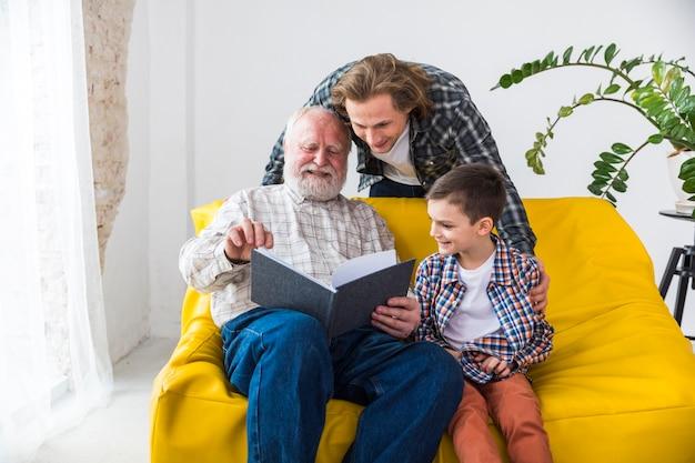 Nette multi generationsfamilie, die durch fotoalbum schaut Kostenlose Fotos