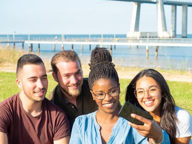 Nette multiethnische leute, die das selfie im freien nehmen Kostenlose Fotos