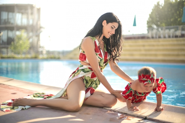 Nette mutter, die mit ihrer tochter nahe bei einem swimmingpool spielt Premium Fotos