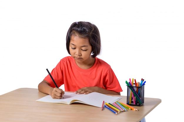 Nette nette kinderzeichnung unter verwendung des farbbleistifts beim bei tisch sitzen lokalisiert auf weißem hintergrund Premium Fotos