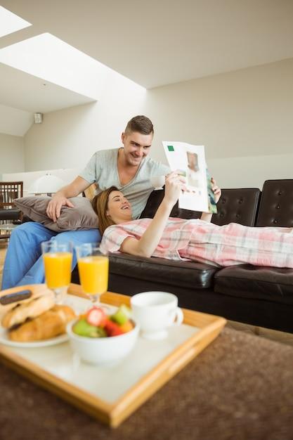 Nette paare, die auf couch am frühstück sich entspannen Premium Fotos