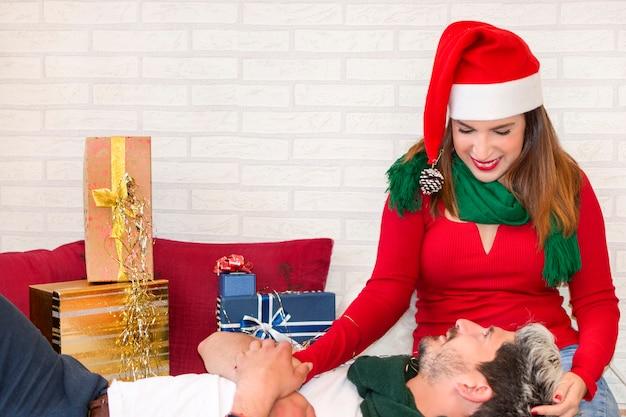 Nette paare in der liebe, die zu hause weihnachten, mit geschenken feiert Premium Fotos