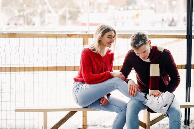 Nette paare in rote strickjacken helfen sich, eiszulaufen Kostenlose Fotos