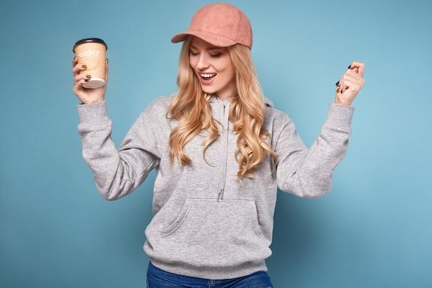 Nette positive blondine in der rosa kappe mit kaffee Premium Fotos