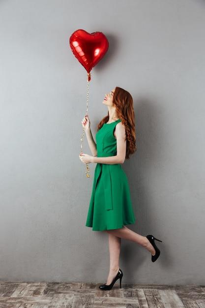 Nette rothaarige junge frau, die herzballon hält. Premium Fotos