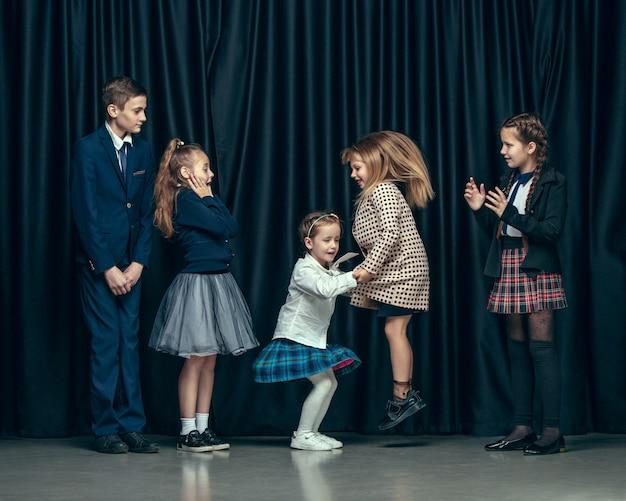 Nette stilvolle kinder auf dunklem raum. die schönen jugendlich mädchen und jungen, die zusammen stehen Kostenlose Fotos