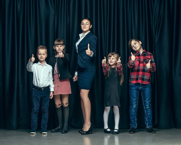 Nette stilvolle kinder auf dunklem studio. die schönen jugendlich mädchen und jungen, die zusammen stehen Kostenlose Fotos