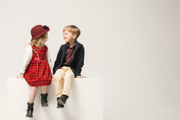 Nette stilvolle kinder auf weißem studio Kostenlose Fotos