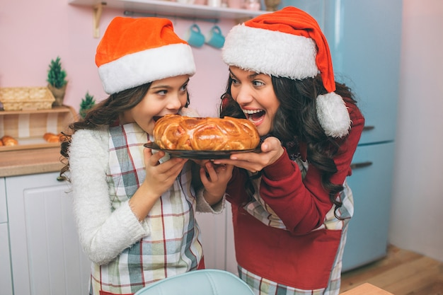 Nette und positive junge frau und mädchen halten platte mit torte und betrachten einander. sie beißen es. frau und mädchen lächeln. sie tragen schürzen und weihnachtsmützen. Premium Fotos