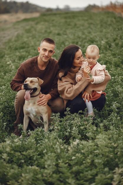 Nette und stilvolle familie, die auf einem gebiet spielt Kostenlose Fotos