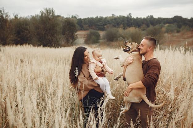 Nette und stilvolle familie, die auf einem herbstgebiet spielt Kostenlose Fotos