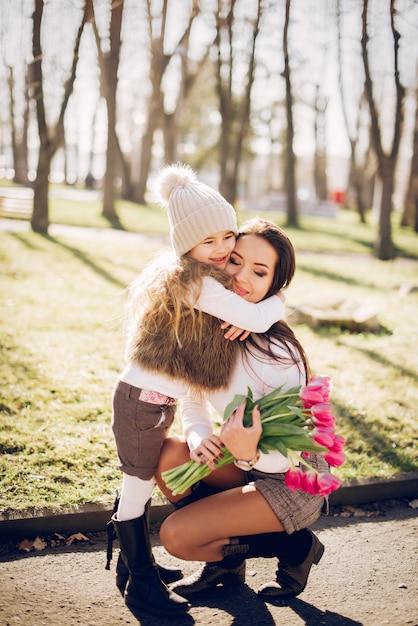 Nette und stilvolle familie in einem frühlingspark Kostenlose Fotos