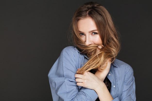 Nette verspielte junge frau bedeckte gesicht mit ihren haaren Kostenlose Fotos