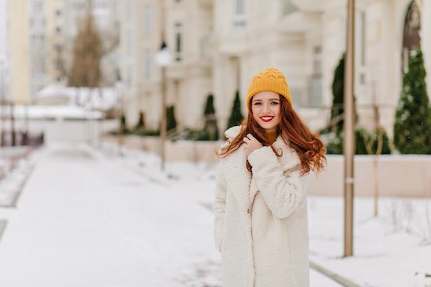 Nette weiße frau, die im wintertag aufwirft. außenfoto der zufriedenen ingwerdame im langen mantel. Kostenlose Fotos