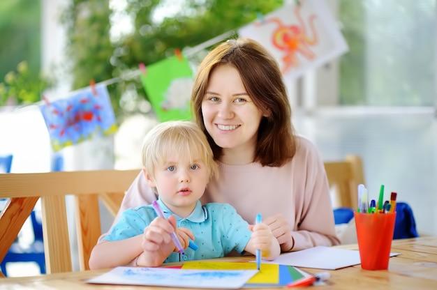 Nette zeichnung und malerei des kleinen jungen mit bunten markierungsstiften am kindergarten Premium Fotos