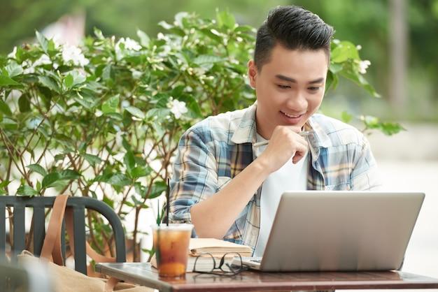 Netter asiatischer mann, der café am im freien sitzt und laptopschirm mit aufregung betrachtet Kostenlose Fotos