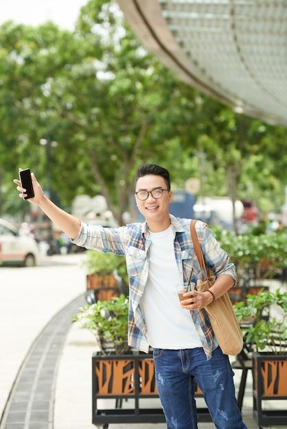 Netter asiatischer mann, der seite der straße bereitsteht und heraus hand mit smartphone haftet Kostenlose Fotos
