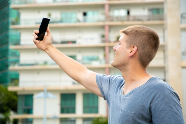 Netter aufgeregter studentenkerl, der draußen selfie nimmt Kostenlose Fotos