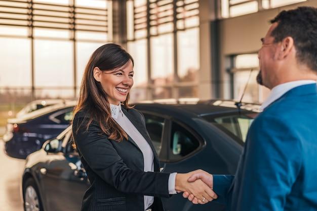 Netter autohändlerhändedruck mit kunden im ausstellungsraum. Premium Fotos
